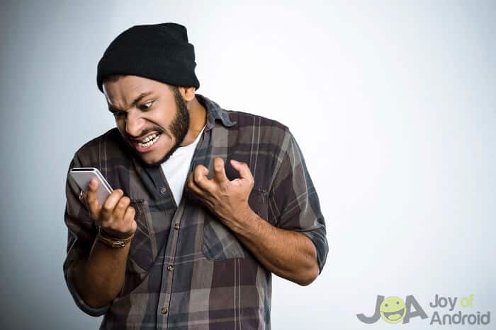 man with beanie angry at phone