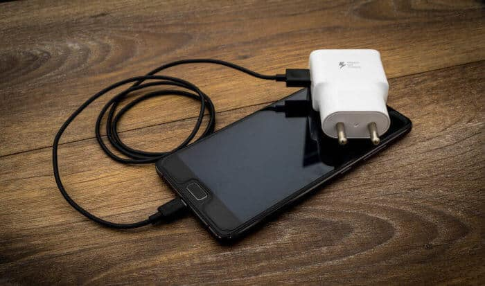 A black mobile phone battery charger with black usb cable