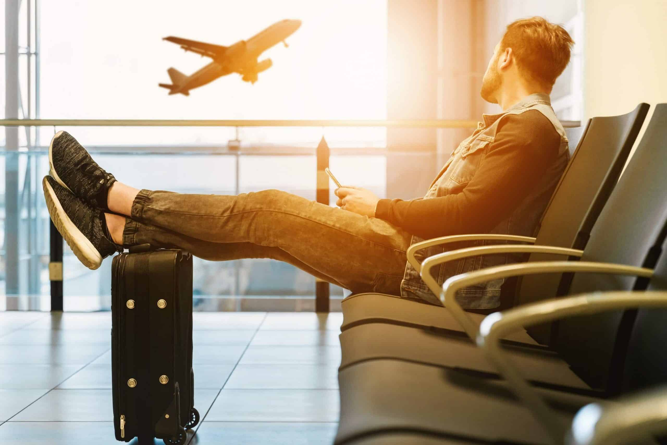 Man Sitting Airport Waiting with Phone feet crossed on luggage bag