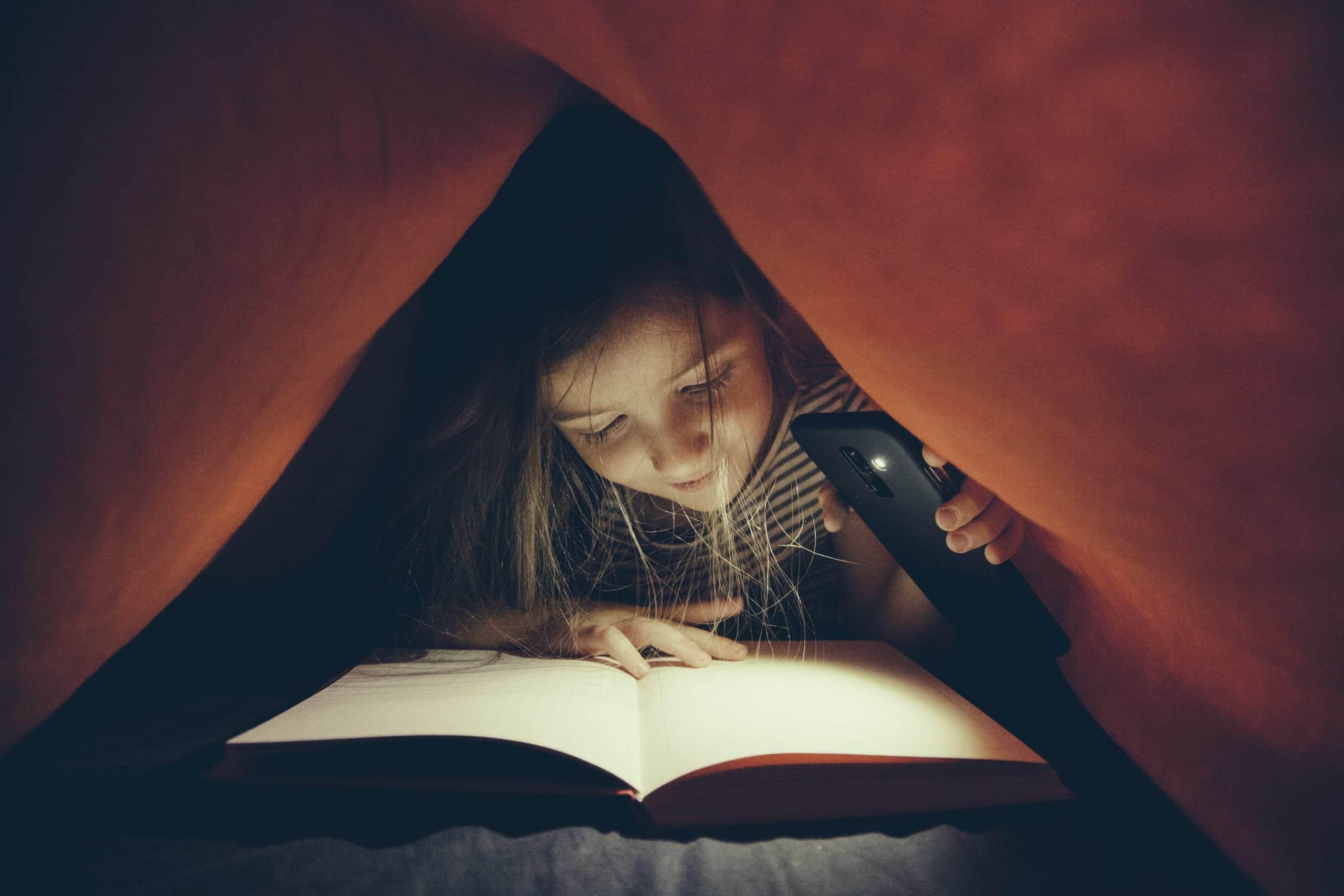 girl studying in dark under flashlight